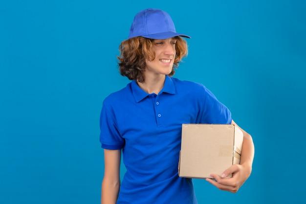 青いポロシャツと段ボール箱を手に保持しているキャップを着ている若い配達人