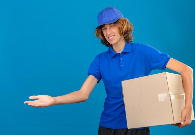 青いポロシャツと分離の青い背景にカメラを見て手のひらで指している大きな段ボール箱を保持しているキャップを着ている若い配達人