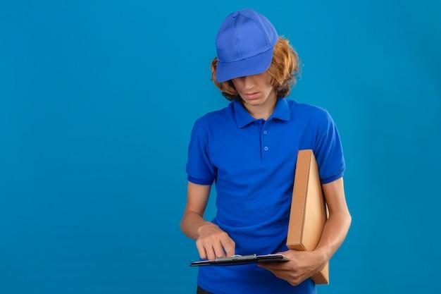 Молодой курьер в синей рубашке поло и кепке, держащий пакет и буфер обмена с пробелами на синем фоне