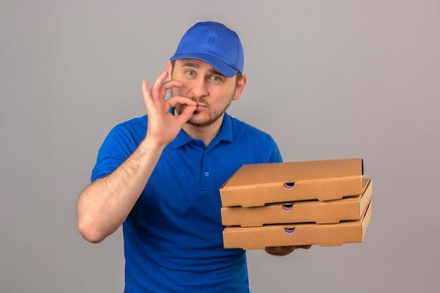 青いポロシャツと分離の白い背景の上の手と口の近くの指でおいしいジェスチャーを示すピザの箱のスタックを保持している若い配達人