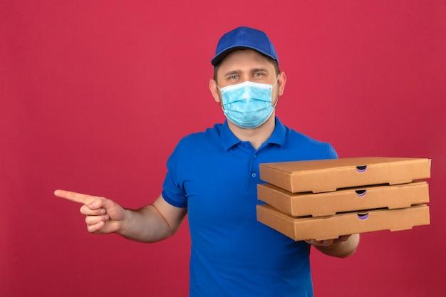 Молодой курьер в синей рубашке поло и кепке в медицинской маске держит стопку коробок для пиццы, указывая пальцем в сторону, стоя на изолированном розовом фоне