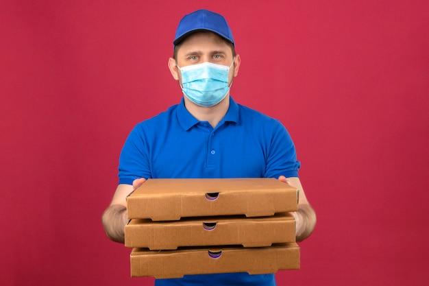 Молодой курьер в синей рубашке поло и кепке в медицинской маске, держащий вытянутую стопку коробок для пиццы, смотрит в камеру с серьезным лицом на изолированном розовом фоне
