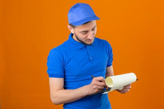 Молодой курьер в синей рубашке поло и кепке смотрит в буфер обмена в руках с серьезным лицом на изолированном оранжевом фоне