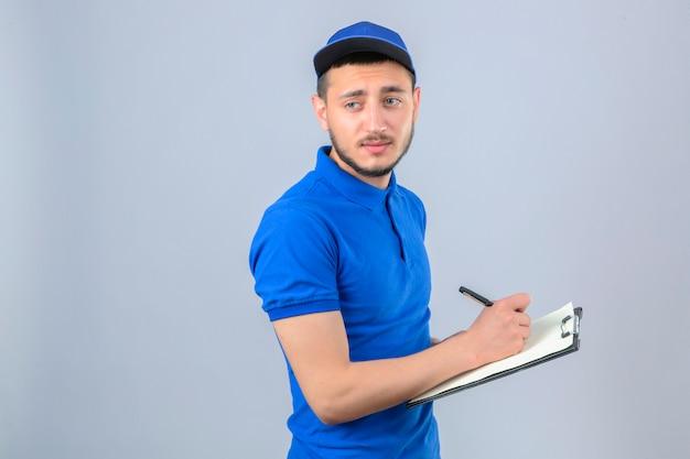 파란색 폴로 셔츠와 모자를 입고 젊은 배달 남자 클립 보드와 함께 서 있고 격리 된 흰색 배경 위에 쓰기 지루 찾고