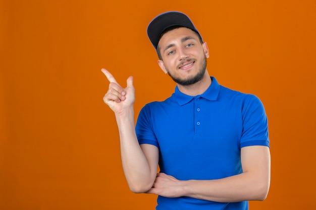 Молодой курьер в синей рубашке поло и кепке, указывая указательным пальцем в сторону, выглядит уверенным и счастливым на изолированном оранжевом фоне