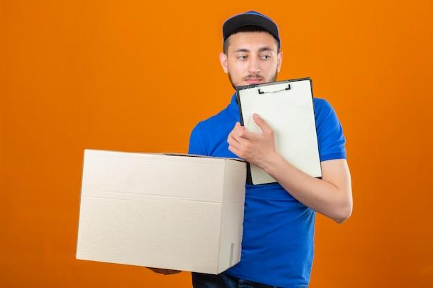Молодой курьер в синей рубашке поло и кепке стоит с большой картонной коробкой и буфером обмена, глядя на изолированный оранжевый фон