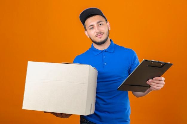 Молодой курьер в синей рубашке поло и кепке, стоящий с картонной коробкой и буфером обмена, смотрит в камеру с улыбкой на лице на изолированном оранжевом фоне