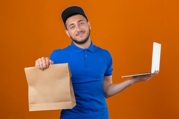 Молодой курьер в синей рубашке поло и кепке, стоящий с буфером обмена и бумажным пакетом, смотрит в камеру с улыбкой на лице на изолированном оранжевом фоне