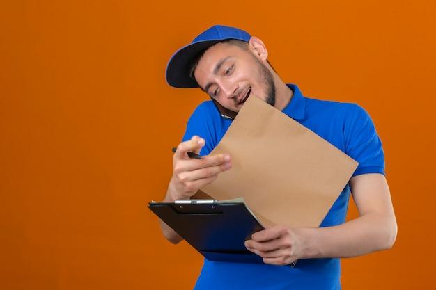 Молодой курьер в синей рубашке поло и кепке, стоящий с буфером обмена и бумажным пакетом, разговаривает по мобильному телефону на изолированном оранжевом фоне