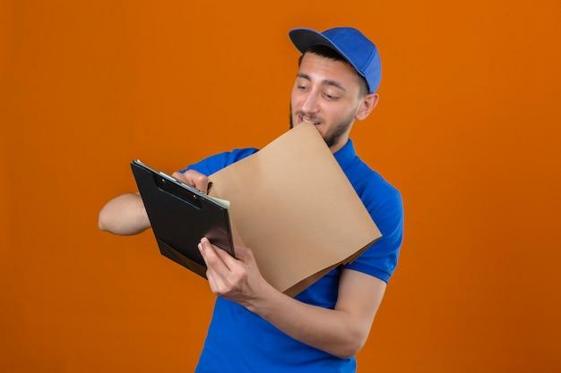Молодой курьер в синей рубашке поло и кепке, стоящий с буфером обмена и написанием бумажного пакета с улыбкой на лице на изолированном оранжевом фоне