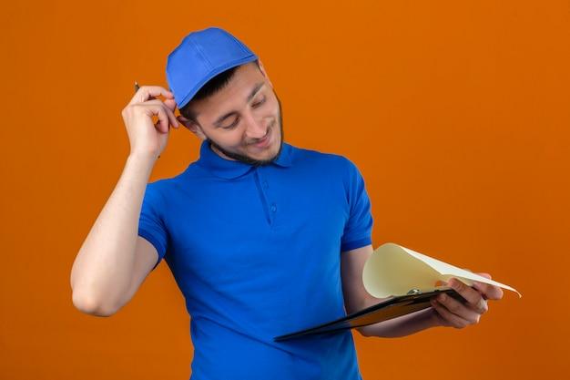 Молодой курьер в синей рубашке поло и кепке, стоящий с буфером обмена, выглядит смущенным и трогательно сомневается на изолированном оранжевом фоне