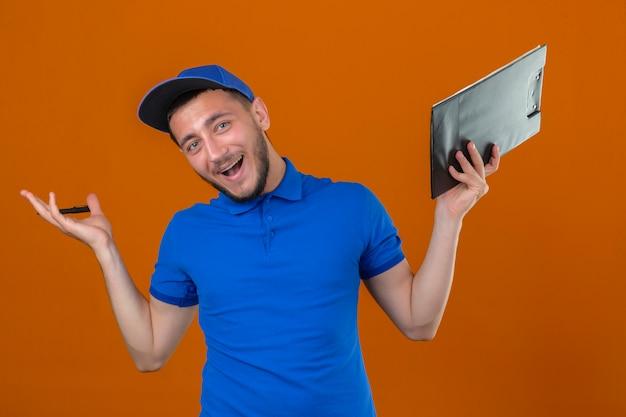 Молодой курьер в синей рубашке поло и кепке, стоящий с буфером обмена со счастливой улыбкой и выражением победителя с поднятой рукой на изолированном оранжевом фоне