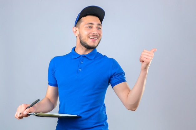 Молодой курьер в синей рубашке поло и кепке, стоя с ручкой и буфером обмена, указывая в сторону и улыбаясь на изолированном белом фоне