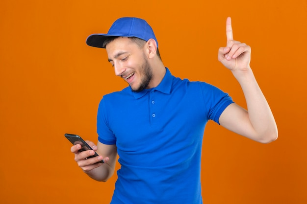 Молодой курьер в синей рубашке поло и кепке стоит со смартфоном в руке, указывая пальцем вверх, улыбаясь новой концепции идеи на изолированном оранжевом фоне