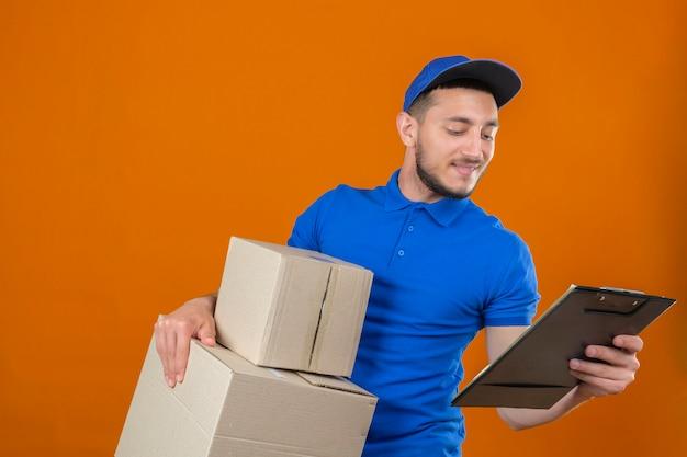 Молодой курьер в синей рубашке поло и кепке, стоящий с стопкой коробок, глядя в буфер обмена с улыбкой на лице на изолированном оранжевом фоне