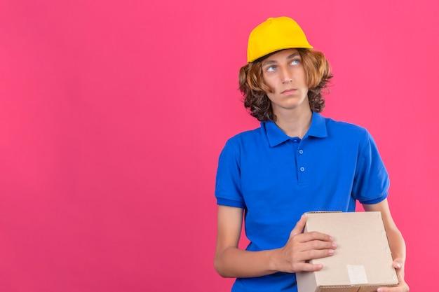 コピースペースと孤立したピンクの背景の上に立っている夢のような表情で見上げると青いポロシャツと段ボール箱を持って黄色のキャップを着ている若い配達人