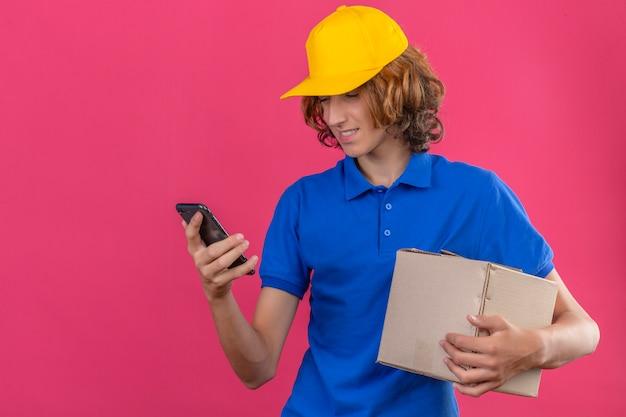 青いポロシャツと黄色の帽子を身に着けている若い配達人