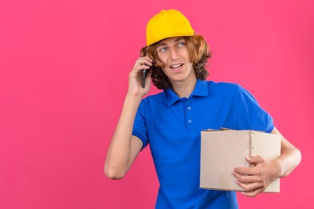 孤立したピンクの背景の上にフレンドリーな立っている笑顔でスマートフォンで話しながら青いポロシャツと段ボール箱を保持している黄色の帽子を着ている若い配達人
