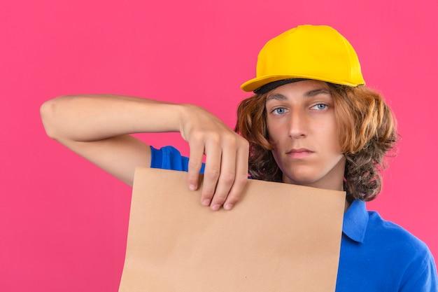 파란색 폴로 셔츠와 격리 된 분홍색 배경 위에 심각한 얼굴로 카메라를보고 손에 종이 패키지를 들고 노란색 모자를 쓰고 젊은 배달 남자
