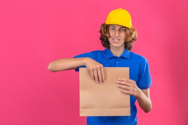 파란색 폴로 셔츠와 격리 된 분홍색 배경 위에 얼굴에 미소로 카메라를보고 손에 종이 패키지를 들고 노란색 모자를 입고 젊은 배달 남자