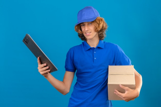 Giovane uomo di consegna che indossa la maglietta polo blu e cappuccio tenendo la scatola della pizza e appunti con spazi vuoti mentre sorridente amichevole in piedi con la faccia felice su sfondo blu isolato