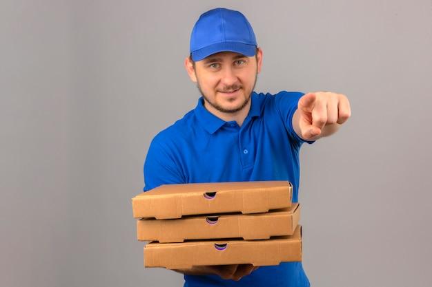 Giovane uomo di consegna che indossa la maglietta polo blu e cappuccio che tiene pila di scatole per pizza che punta alla telecamera con il dito sorridente su sfondo bianco isolato