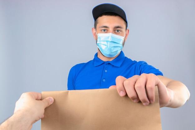 Giovane uomo di consegna che indossa la maglietta polo blu e il cappuccio nella mascherina medica protettiva che dà il pacchetto di carta a un cliente con sguardo fiducioso sopra fondo bianco isolato