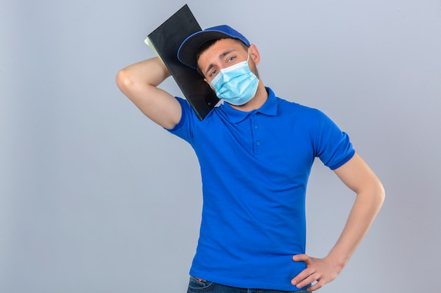 Young delivery man wearing blue polo shirt and cap in protective medical mask standing with clipboard on shoulder looking tired and bored over isolated white background