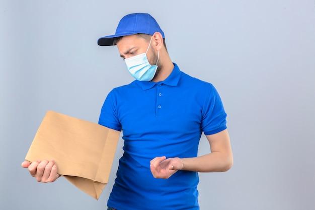 Giovane uomo di consegna che indossa la maglietta polo blu e il cappuccio nella mascherina medica protettiva in piedi con il pacchetto di carta avendo dubbi con l'espressione del viso confuso su sfondo bianco isolato