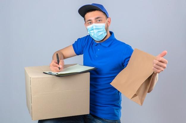 Giovane uomo di consegna che indossa la maglietta di polo blu e cappuccio nella mascherina medica protettiva che sta con il pacchetto di carta che scrive sulla scatola negli appunti sopra fondo bianco isolato