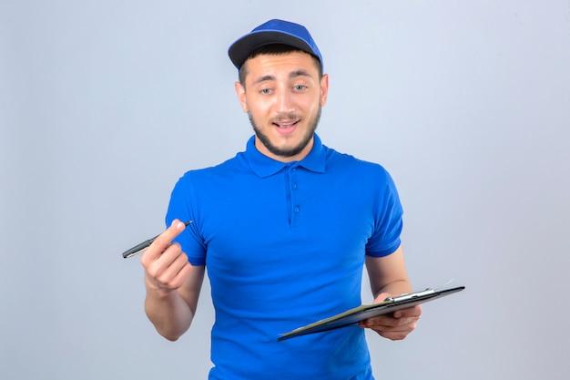 Giovane uomo di consegna indossando polo blu e cappuccio in piedi con appunti e penna su sfondo bianco isolato