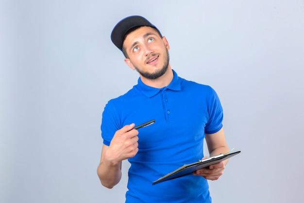 Giovane uomo di consegna che indossa la maglietta polo blu e cappuccio in piedi con appunti e penna cercando con il sorriso sul viso su sfondo bianco isolato