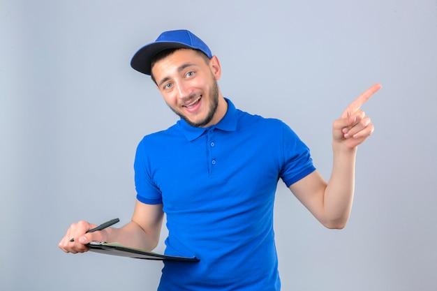 Giovane uomo di consegna che indossa la maglietta polo blu e cappuccio in piedi con la penna e indicando il lato con il dito su sfondo bianco isolato