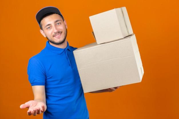 Giovane uomo di consegna indossando polo blu e cappuccio in piedi con la pila di scatole che guarda l'obbiettivo con sorriso in attesa di pagamento per la consegna su sfondo arancione isolato
