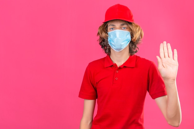Молодой курьер в красной рубашке поло и кепке в медицинской маске, стоящий с открытой рукой, делает знак остановки с серьезным и уверенным жестом защиты на розовом фоне