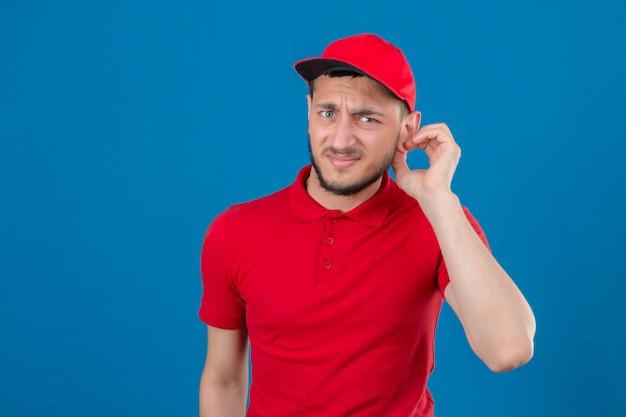 赤いポロシャツと彼の耳に触れるカメラを見てキャップを着ている若い配達人は孤立した青い背景の上に横になっている誰かを聞いてはいけない