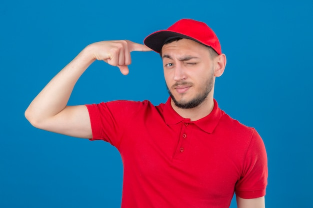 Молодой курьер в красной рубашке поло и кепке смотрит в камеру, подмигивая, указывая указательным пальцем на голову, выглядит умно на изолированном синем фоне