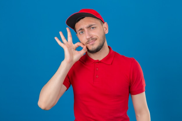 Молодой курьер в красной рубашке поло и кепке делает жест молчания, словно закрывает рот застежкой-молнией на изолированном синем фоне