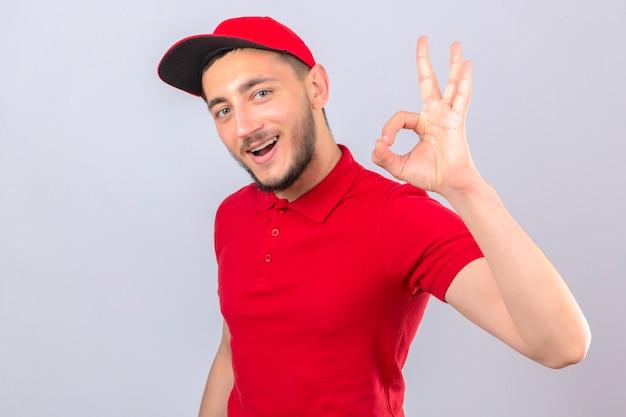 Молодой курьер в красной рубашке поло и кепке, весело улыбаясь, делает хорошо подписывается на изолированном фоне