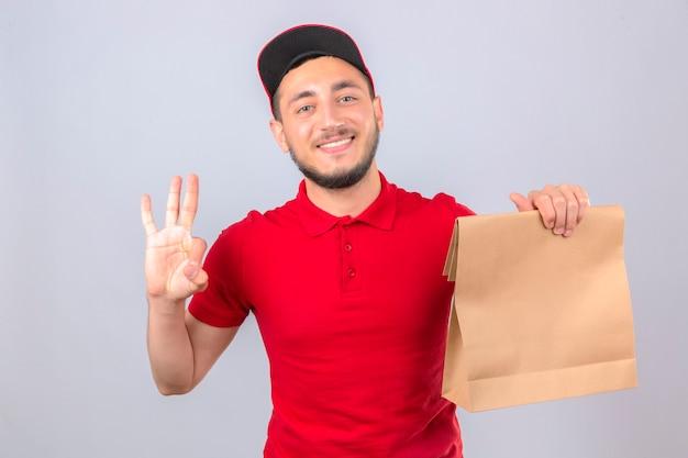 分離した白い背景に自信を持って、幸せな笑顔で赤いポロシャツとキャップ立って紙パッケージを示し、指番号3で上向きに身に着けている若い配達人