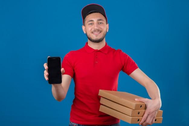赤いポロシャツとピザの箱のスタックで立っているキャップを着て、孤立した青い背景にカメラを見てフレンドリーな笑顔のスマートフォンを示す若い配達人