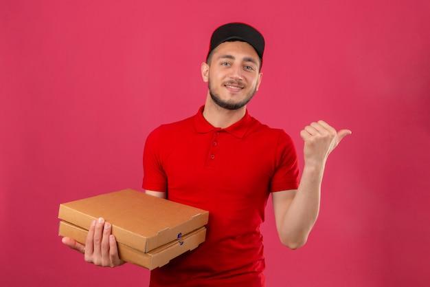 Молодой курьер в красной рубашке поло и кепке, стоящий с стопкой коробок для пиццы, указывая и показывая большим пальцем в сторону со счастливым лицом, улыбающимся на изолированном розовом фоне