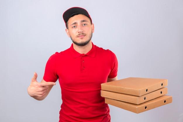 Молодой курьер в красной рубашке поло и кепке, стоящий со стопкой коробок для пиццы, указывая на них пальцем, уверенно выглядящий на изолированном фоне