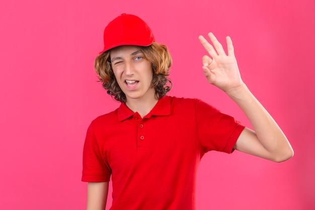 Молодой курьер в красной рубашке поло и кепке, подмигивая, глядя в камеру с улыбкой, делает хорошо, знак стоит на изолированном розовом фоне