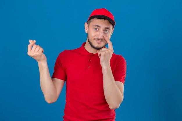 Молодой курьер в красной рубашке поло и кепке беспокоится о деньгах, делая денежный жест рукой на изолированном синем фоне
