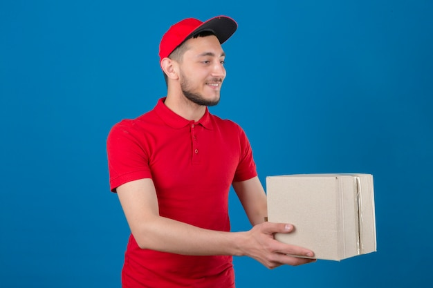 Giovane uomo di consegna che indossa la maglietta polo rossa e cappuccio dando la scatola di cartone al cliente con il sorriso sul viso isolato su sfondo blu