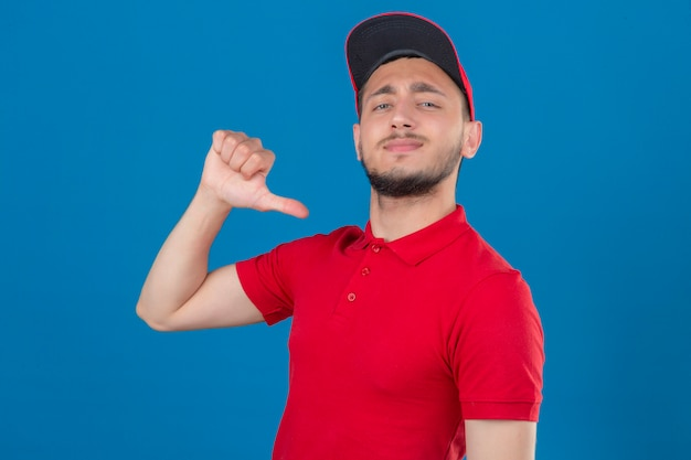 Young delivery man wearing red polo shirt and cap looking at camera smiling cheerfully proud and self-satisfied over isolated blue background