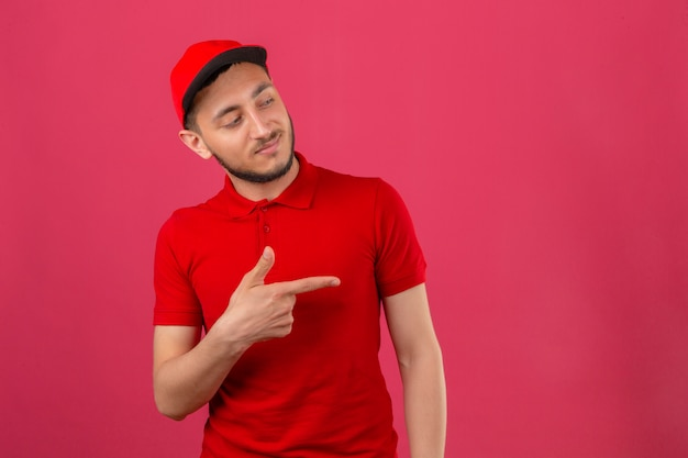 Young delivery man wearing red polo shirt and cap pointing to the side to present something over isolated pink background
