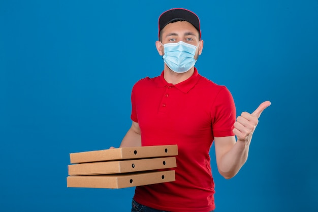 Young delivery man wearing red polo shirt and cap in protective medical mask standing with stack of pizza boxes showing thumb up over isolated blue background