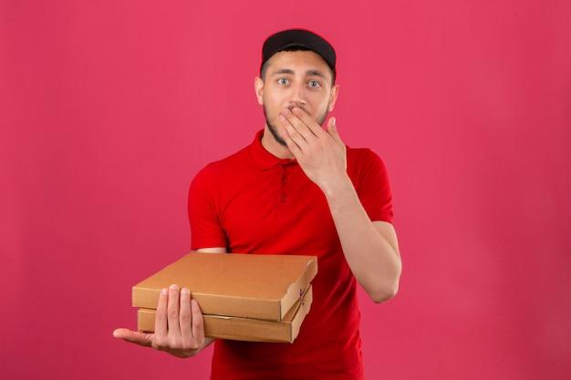 Giovane uomo di consegna che indossa la maglietta polo rossa e cappuccio in piedi con scatole per pizza guardando sorpreso e scioccato che copre la bocca su sfondo rosa isolato
